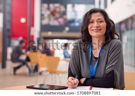 Portrait Of Mature Female Teacher Or Student With Digital Tablet Working At Table In College Hall