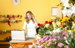 Portrait of mature flower shop owner using her telephone and laptop to take delivery service for her store.