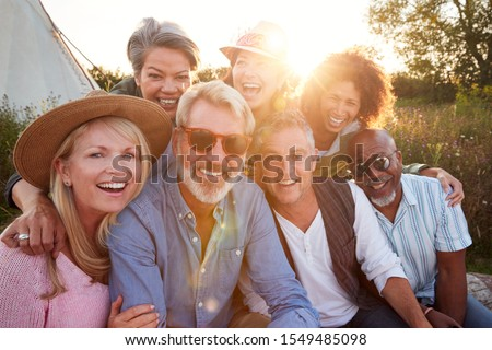 Portrait Of Mature Friends By Tent On Camping Vacation Against Setting Sun
