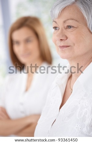 Portrait of mature lady smiling, daughter standing at background.?