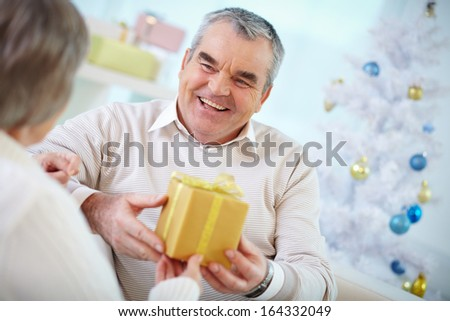 Portrait of mature man giving Christmas present in box to his wife