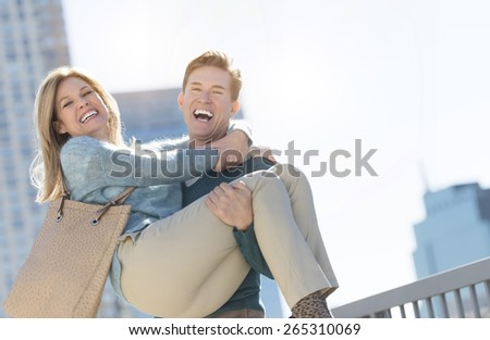 Portrait of mature man laughing while lifting woman in city