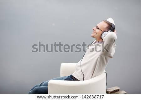 Portrait of mature man listening musing through headphones on pier
