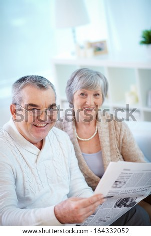 Portrait of mature man reading newspaper at home with his wife near by