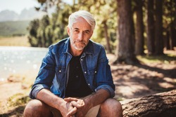 Portrait of mature man sitting near a lake staring at camera. Senior caucasian man relaxing on a log by the lake on a summer day.