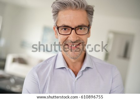 Portrait of mature man with eyeglasses and grey hair - Shutterstock ID 610896755