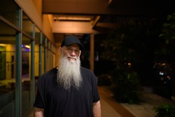 Portrait of mature man with gray beard outdoors at night