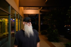 Portrait of mature man with gray beard outdoors at night thinking