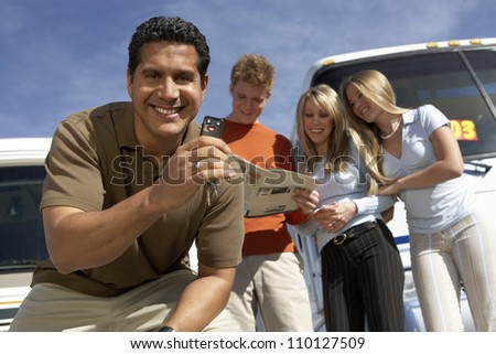 Portrait of mature man with keys to RV with customers
