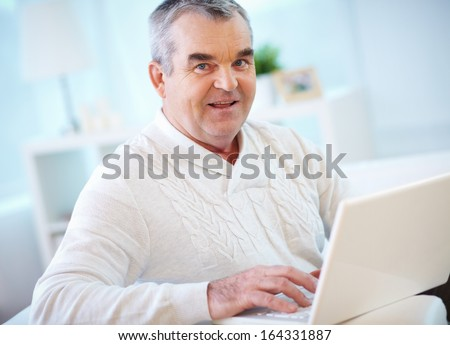 Portrait of mature man working with laptop and looking at camera