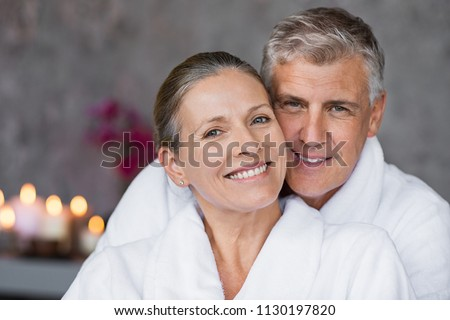 Portrait of mature married couple embracing with bathrobe and looking at camera. Happy senior man and beautiful woman in robes smiling at wellness center. Man and wife relaxing together at day spa. Stock foto ©