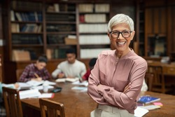 Portrait of mature professor standing in university library and looking at camera with copy space. Happy senior woman at the library working as a librarian. Satisfied college teacher smiling.