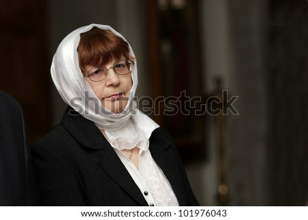 Portrait of mature serious woman in church
