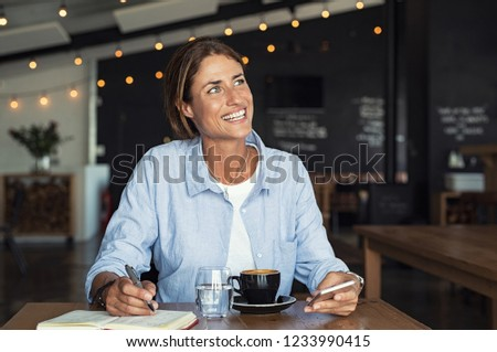 Portrait of mature smiling woman looking away while sending phone message. Middle aged writer sitting in modern cafe. Cheerful mid woman writing in book and using phone at cafeteria while daydreaming.
