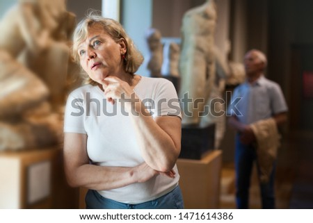 Portrait of mature woman at hall of Art Museum among exhibits of antiquity