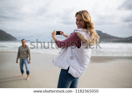 Portrait of mature woman clicking a picture of man on the beach