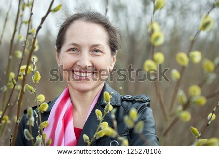 portrait of mature woman in spring pussywillow plant