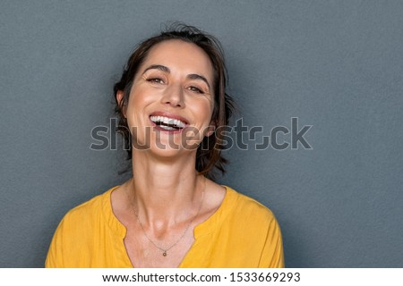 Portrait of mature woman laughing against grey background. Successful middle aged woman in casual with toothy smile looking at camera. Cheerful happy beautiful latin lady smiling with copy space. #1533669293