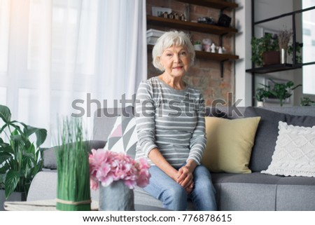 Portrait of mature woman resting on comfortable couch at home. She is smiling and looking at camera #776878615