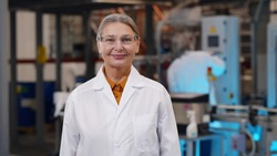Portrait of mature woman scientist in protective glasses and lab coat standing at chemical manufacturing. Aged female engineer looking at camera over heavy industry plant background