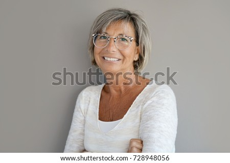Portrait of mature woman with eyeglasses on grey background #728948056
