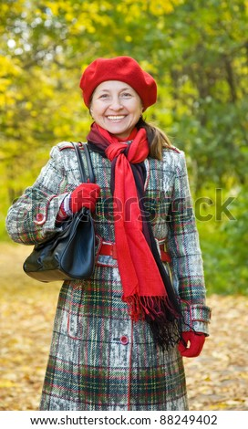 Portrait of mature woman with handbag in autumn park
