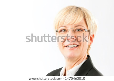 Portrait of matured business woman with golden hair wearing spectacles and black suit standing isolated on white background looking at camera