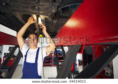portrait of mechanic standing under car and looking at camera. Copy space