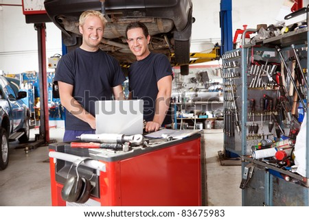 Portrait of mechanics with laptop in auto repair shop