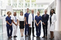 Portrait Of Medical Staff Standing In Lobby Of Hospital