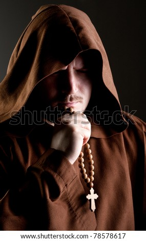 Portrait of medieval monk with cross rosary in shadow