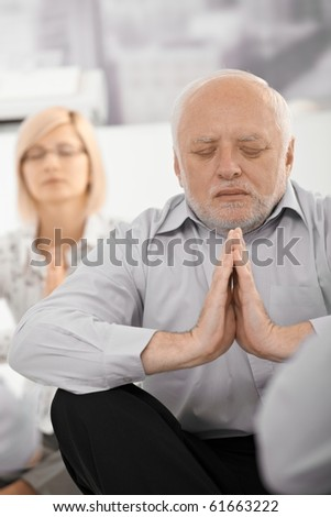 Portrait of meditating senior businessman with hands put together, eyes closed, wearing formal dress in office.?