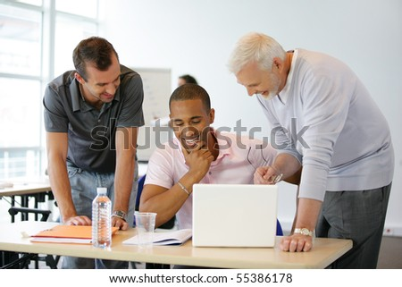 Portrait of men in front of a laptop computer