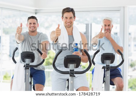 Portrait of men on exercise bikes gesturing thumbs up at gym