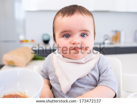 Portrait of messy baby boy eating food in kitchen