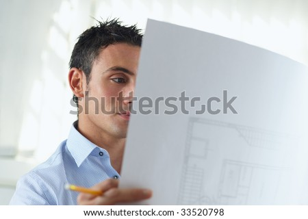 portrait of mid adult architect reading blueprint and smiling