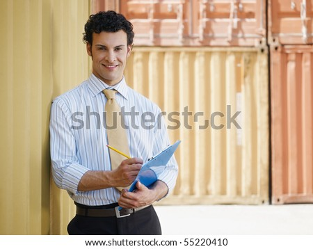 portrait of mid adult businessman leaning on cargo container and looking at camera. Horizontal shape, front view, copy space