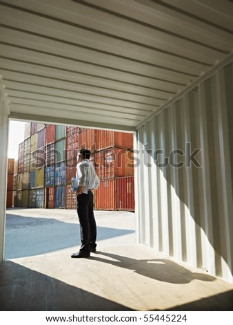 portrait of mid adult businessman standing near cargo container. Vertical shape, side view, copy space