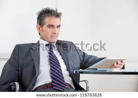 Portrait of mid adult businessman using digital tablet at desk in office