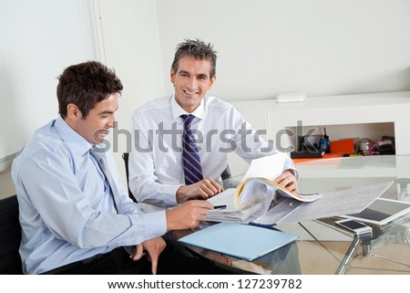 Portrait of mid adult businessman with colleague discussing paperwork at a meeting in office