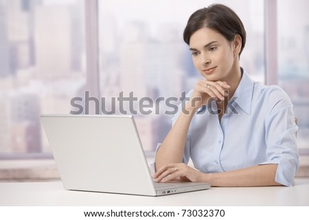 Portrait of mid adult businesswoman sitting at skyscraper office table looking at laptop computer screen.?