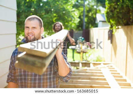 Portrait of mid adult carpenter and coworker carrying lumbers at construction site