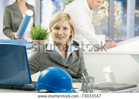 Portrait of mid-adult designer in architect office, smiling at camera,?