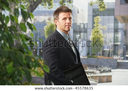 Portrait of mid-adult executive businessman standing in front of office building with briefcase looking at camera smiling.