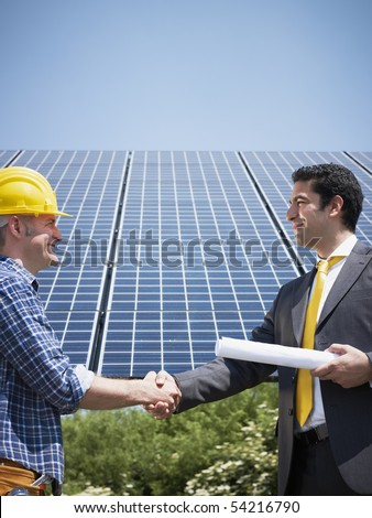 Portrait of mid adult italian male engineer holding blueprints and shaking hands to manual worker in solar power station. Vertical shape, side view. Copy space