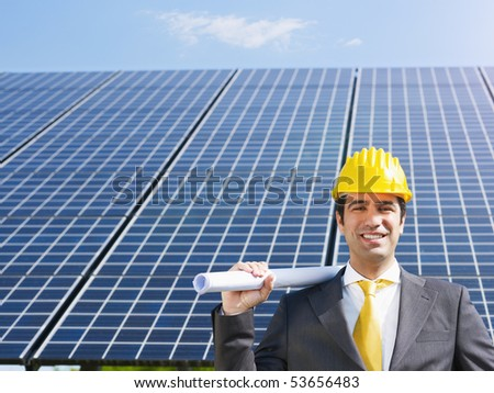 Portrait of mid adult italian male engineer holding blueprints in solar power station and smiling at camera.Horizontal shape, front view. Copy space