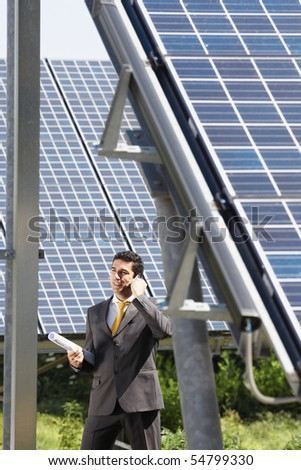 Portrait of mid adult italian male engineer holding blueprints in solar power station and talking on mobile phone. Vertical shape, side view. Copy space