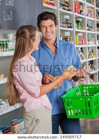 Portrait of mid adult man with woman shopping in grocery store
