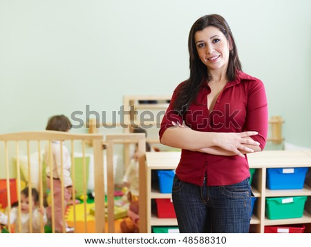 portrait of mid adult teacher in kindergarten. Little girls playing with toys in background. Horizontal shape, copy space - stock photo