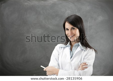 portrait of mid adult teacher with arms folded against blank blackboard. Copy space